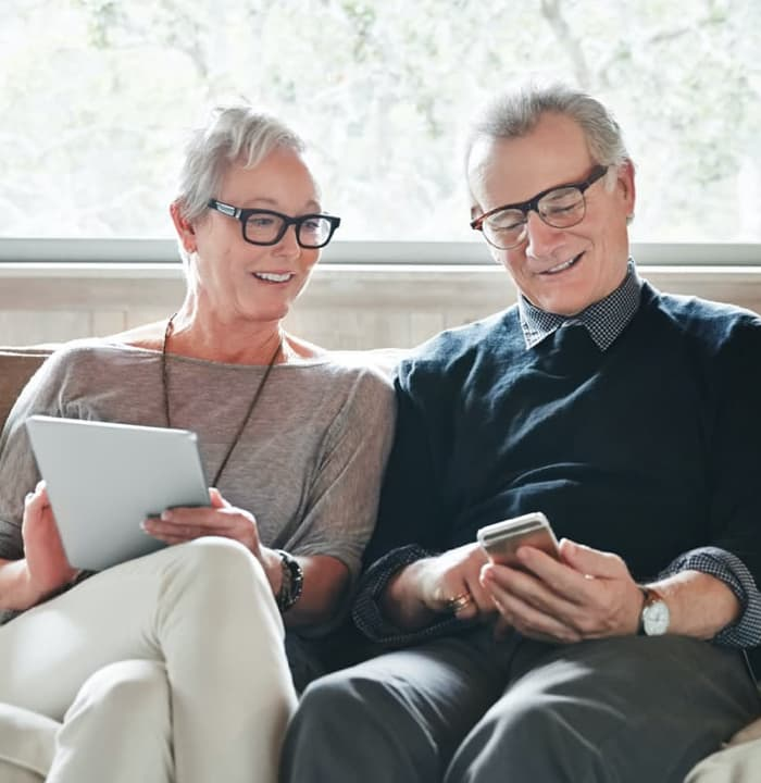 senior couple is looking at their mobile devices with smile